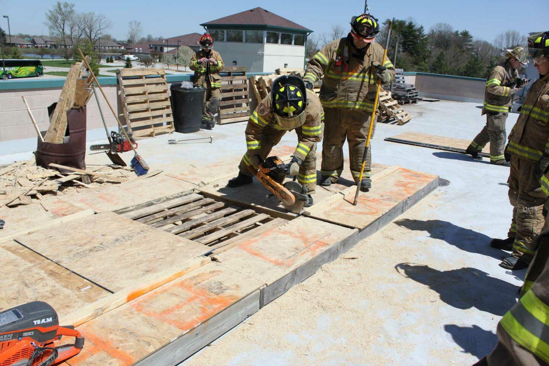 Firefighter guiding a cutting firefighter during a roof cut