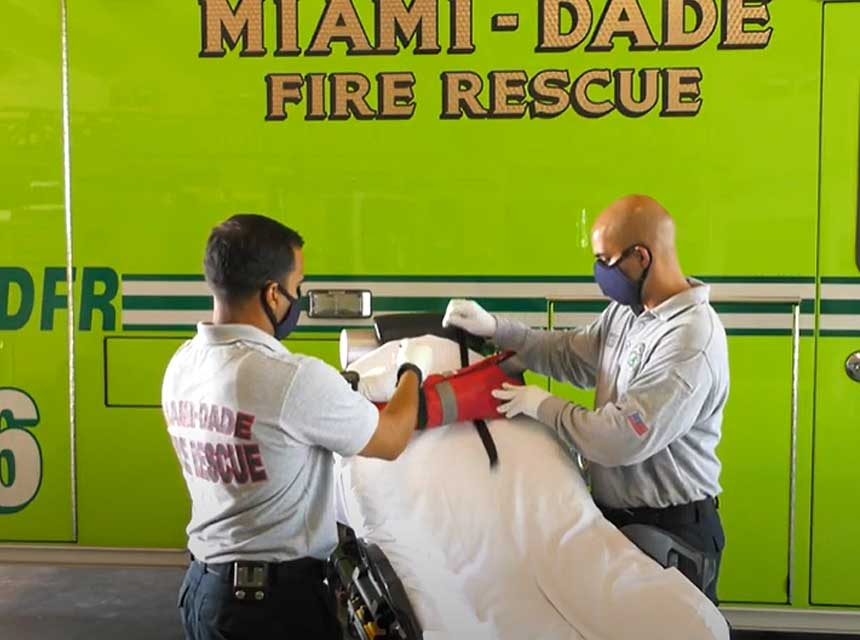 Miam-Dade fire medics work on stretcher in front of ambulance