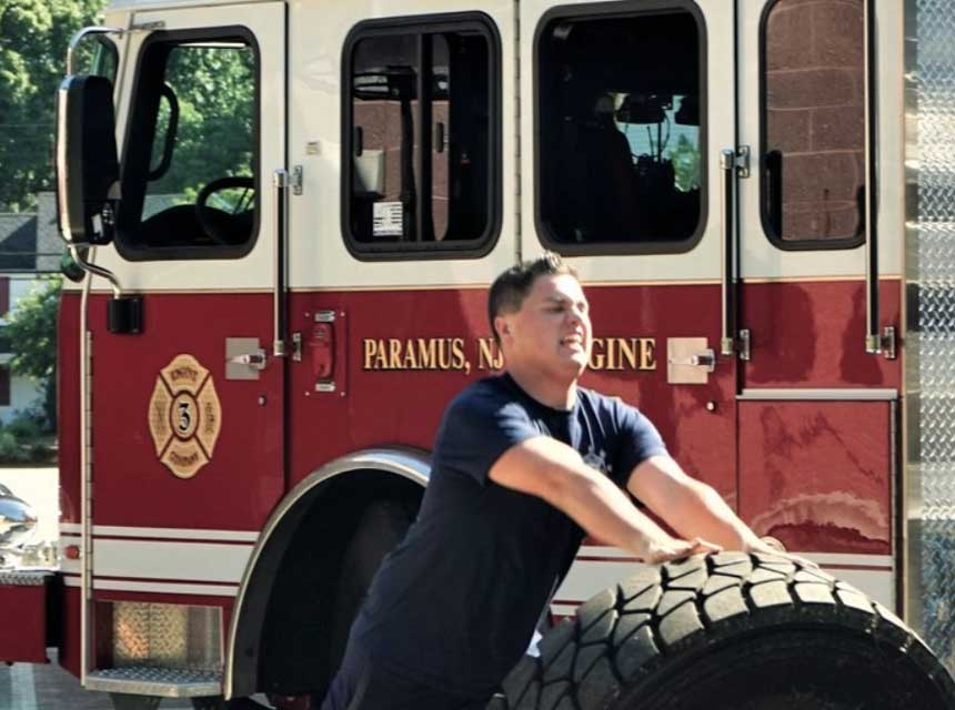 Firefighter rolling a tire in front of fire truck