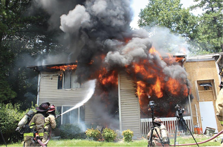 Firefighter applying exterior stream on structure