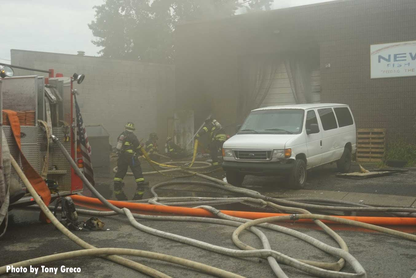 Firefighters maneuvering into fire building amid hoselines