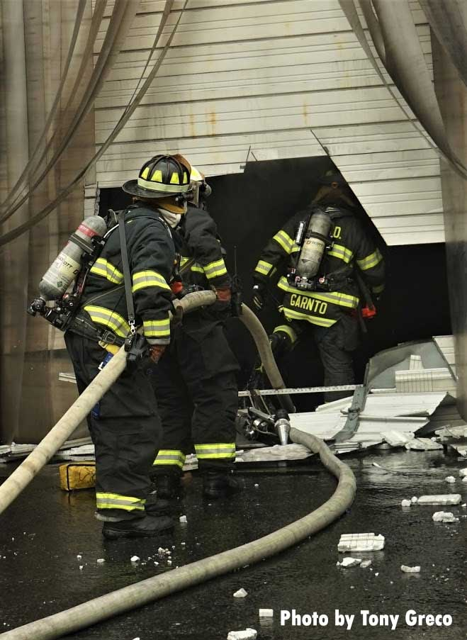 Firefighters move hoslines through hole cut into roll-down door
