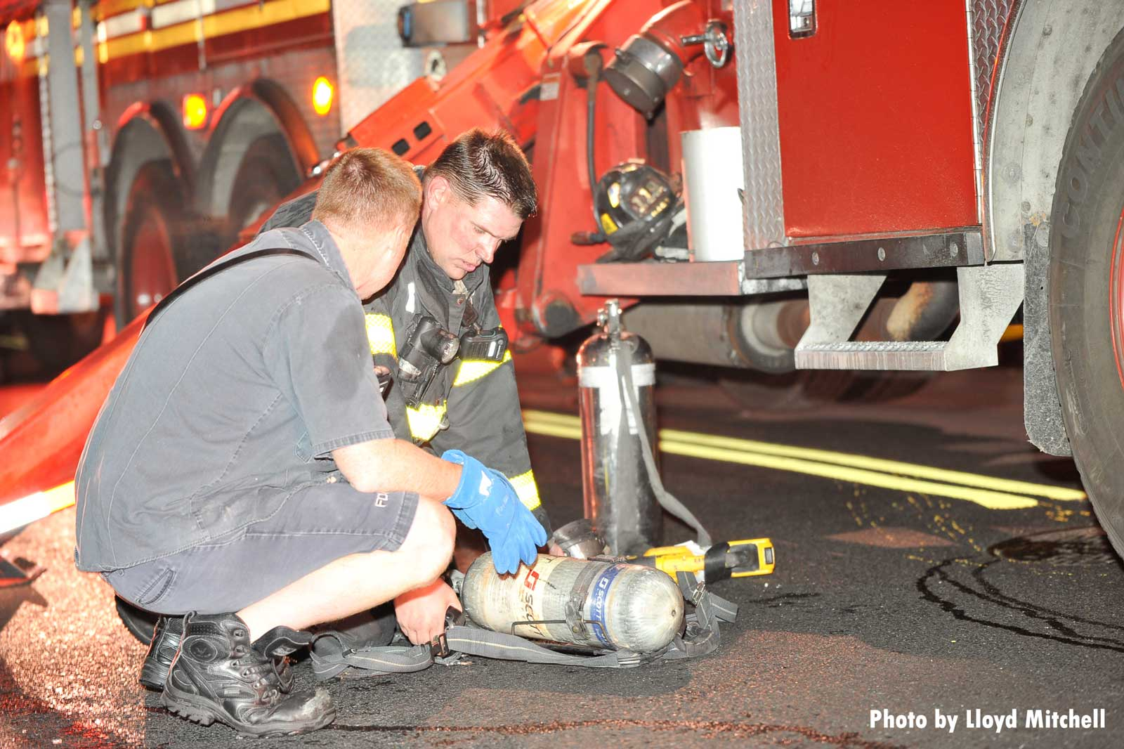Firefighters work with an SCBA bottle at a fire scene
