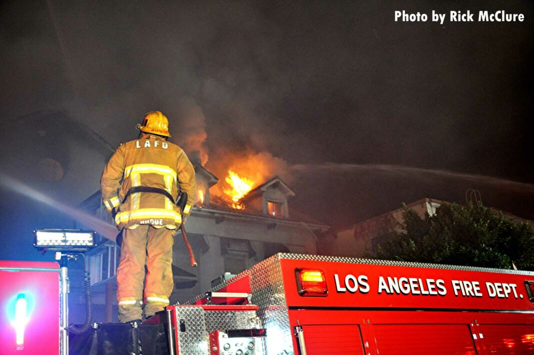 LAFD firefighter on apparatus with flames in background
