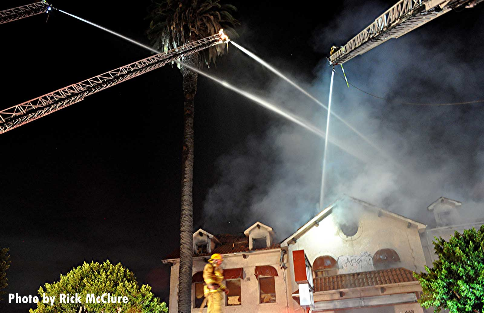 Three master streams from aerials pour water on the flames