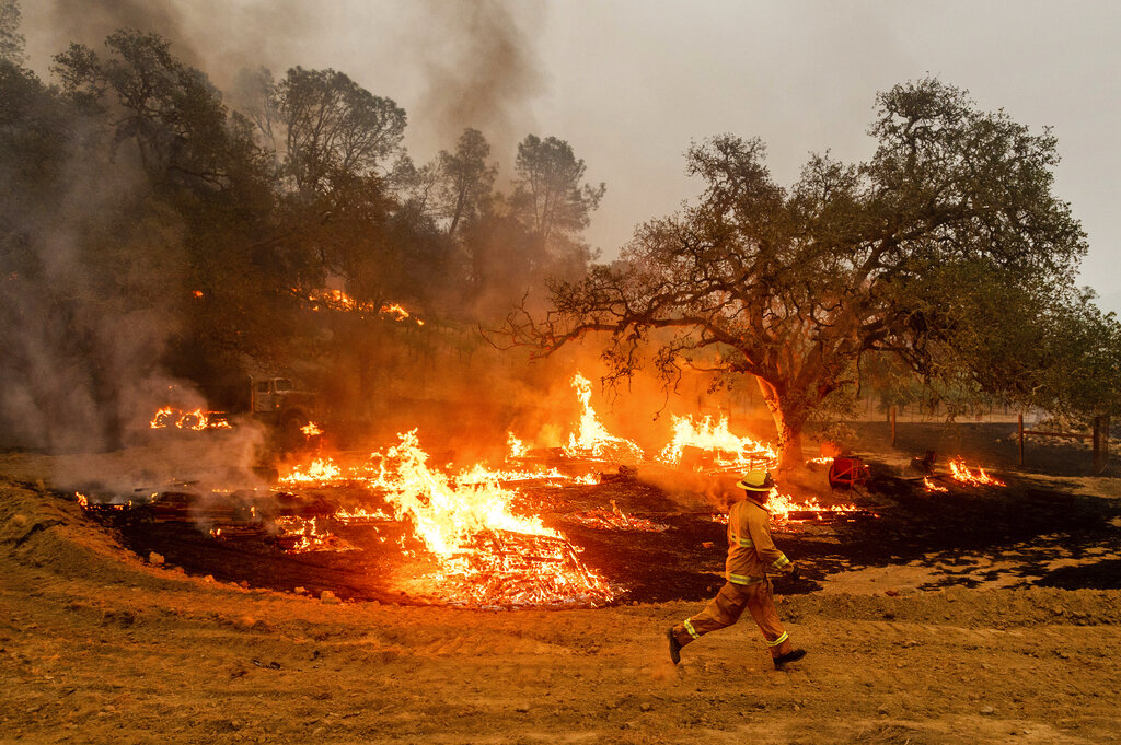 Firefighter runs past flames in California