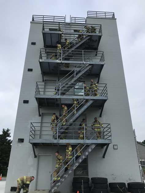 Members of Recruit Class 27 undertake a tower climb in full PPE.