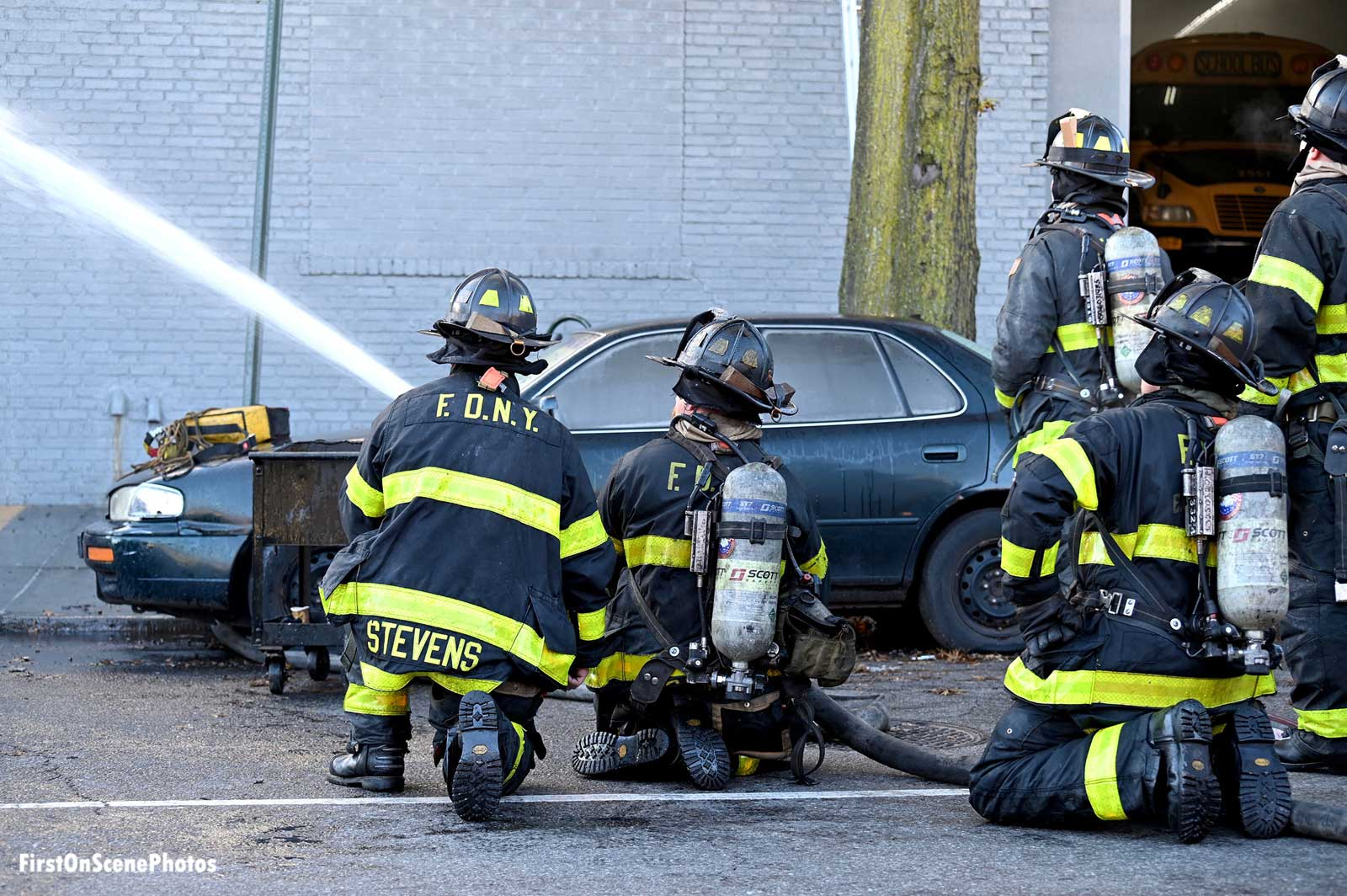 Firefighters train a hose stream into the building