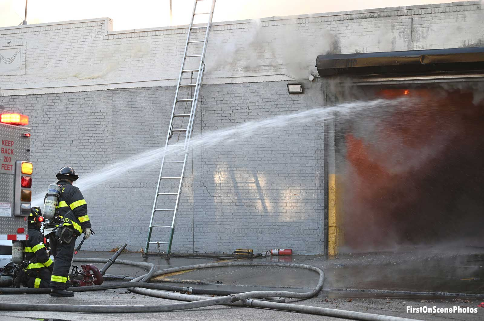 FDNY firefighters with a hose stream