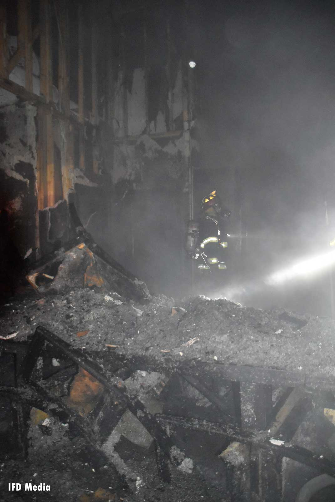 Firefighter amid the ruins of a house fire