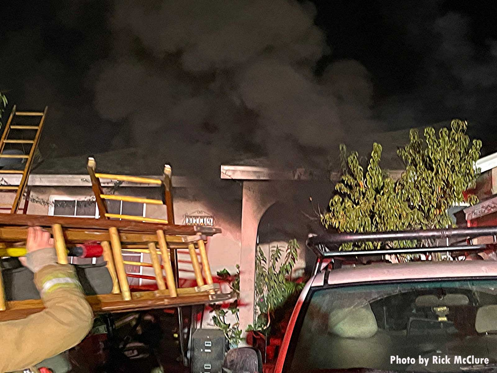 Thick black smoke from house fire with firefighter carrying a ladder