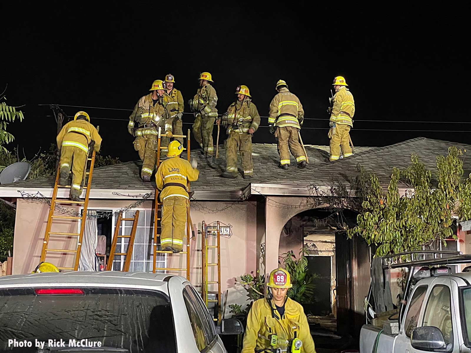 Firefighters ascend to the roof of the building with two ladders on the home