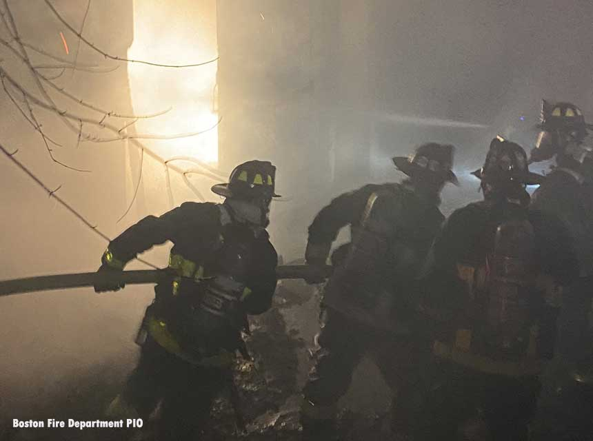 Boston firefighters haul hose at a three-alarm fire