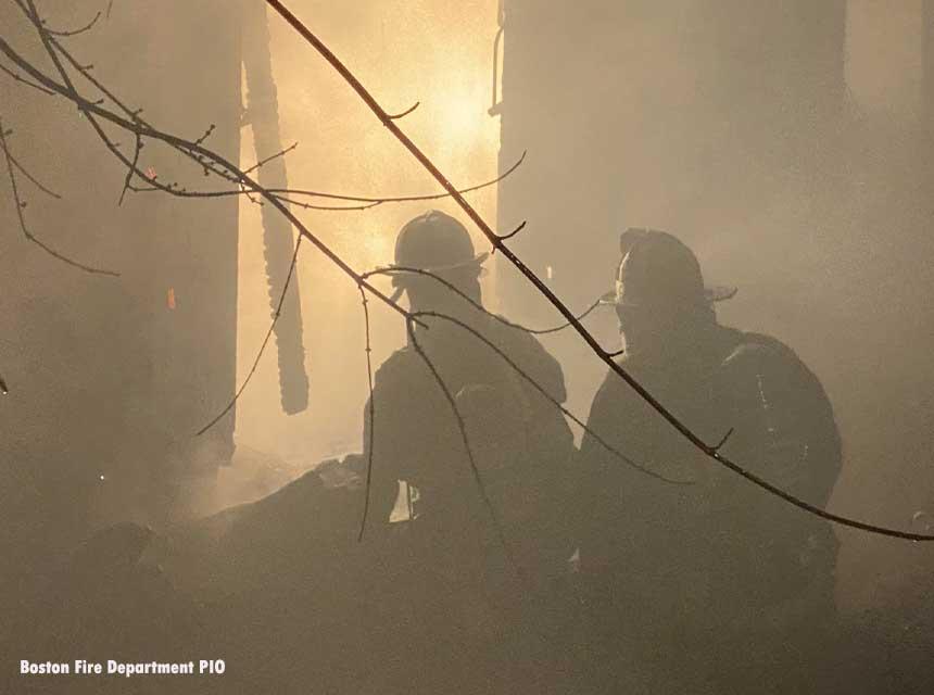 Boston firefighters framed by firelight