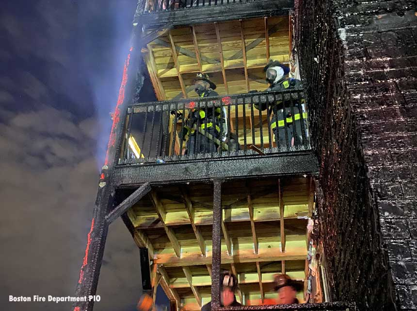 Boston firefighters on the charred deck of a home