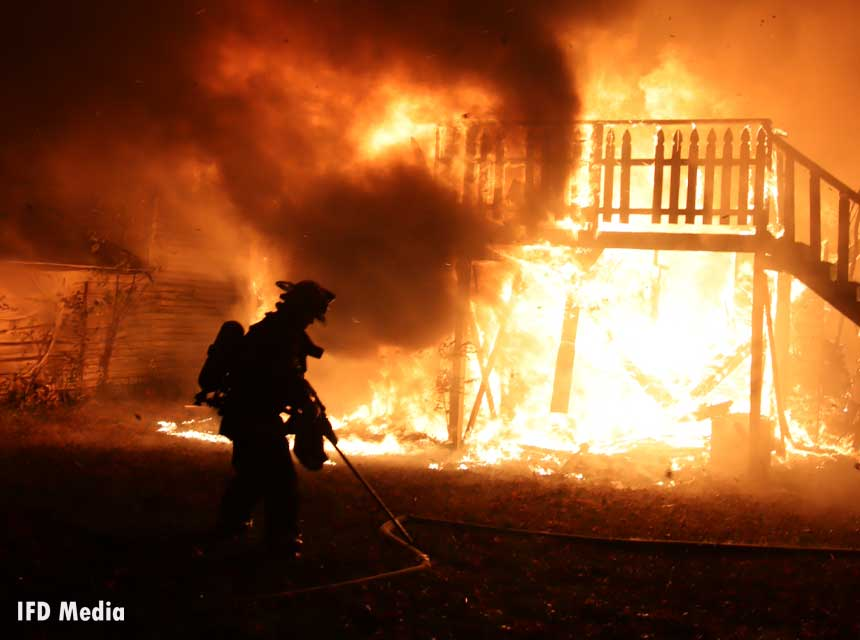 Firefighter silhouetted by flames at fire in Indiana