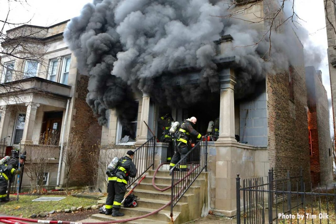 Smoke shoots from a building as Chicago firefighters make entry