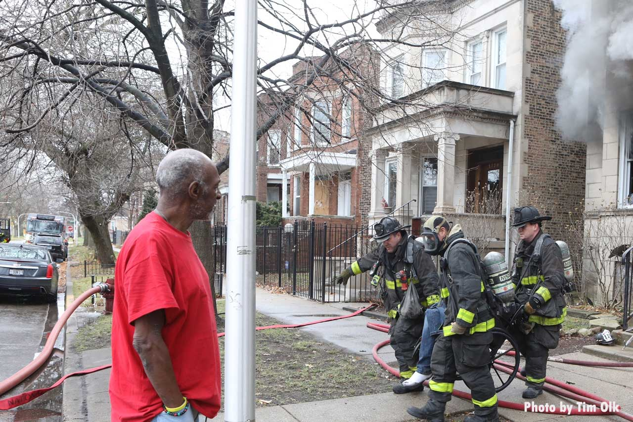 Chicago firefighters pull a victim from a fire as a civilian bystander looks on