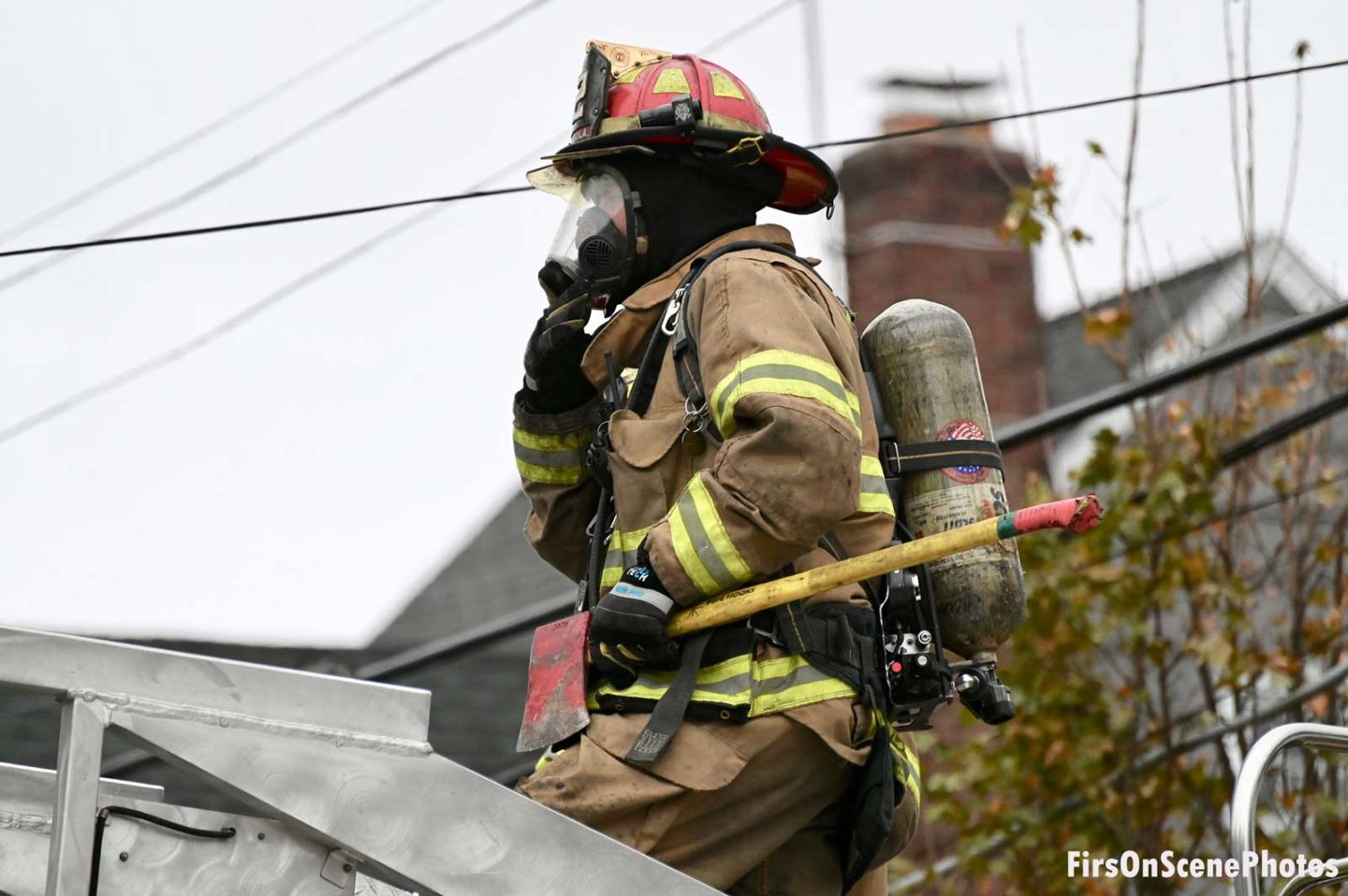 A firefighter in full PPE and SCBA with an ax