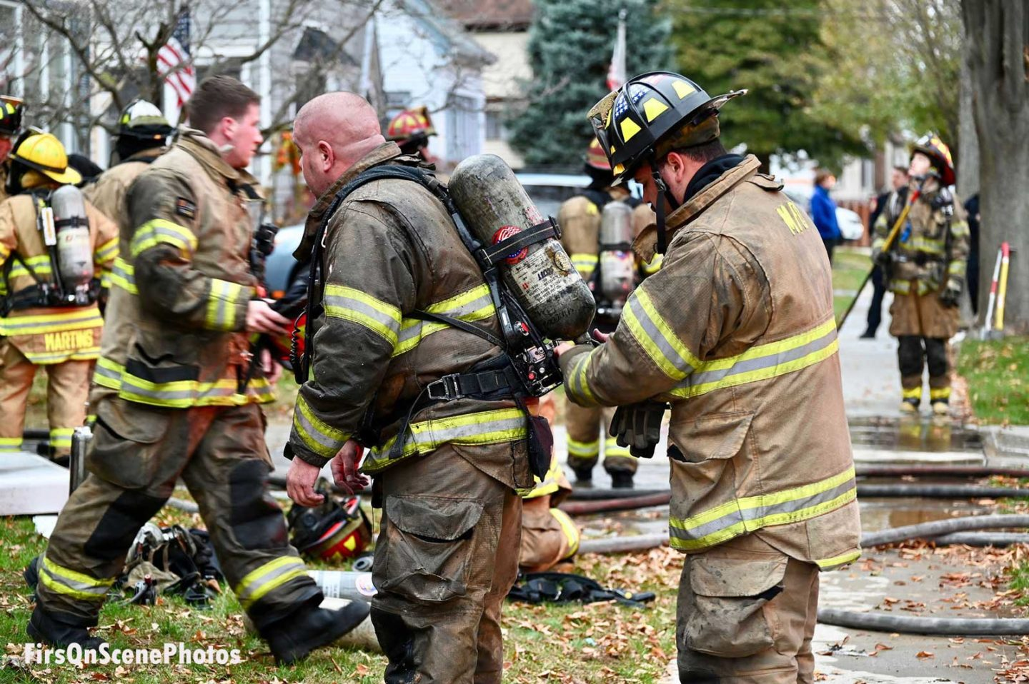Firefighter helping another with his SCBA at the fire scene