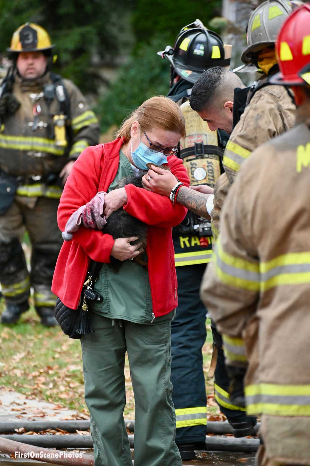 A resident cuddles a dog that firefighters rescued from a fire as firefighters look on