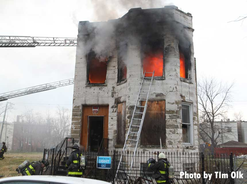 Firefighters battle flames at a vacant building in Chicago with ladder at front of home