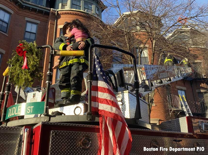 Boston firefighter with a rescued child in a bucket