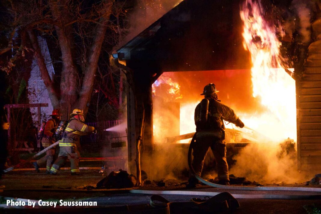 Firefighters put water on flames shooting from a garage in Pennsylvania