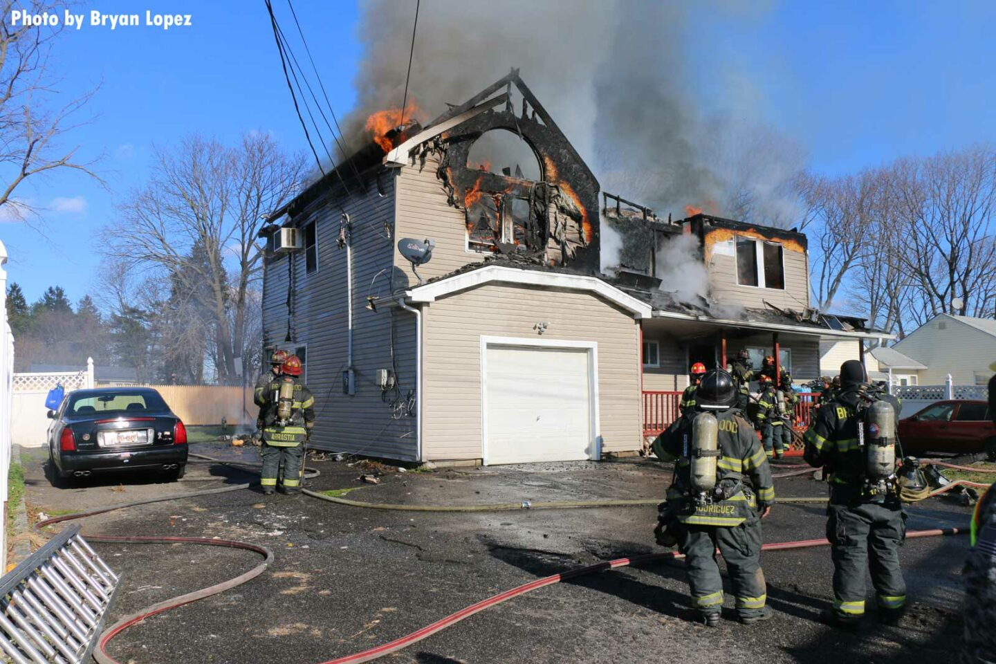Another view of the home, with flames visible and firefighters at work