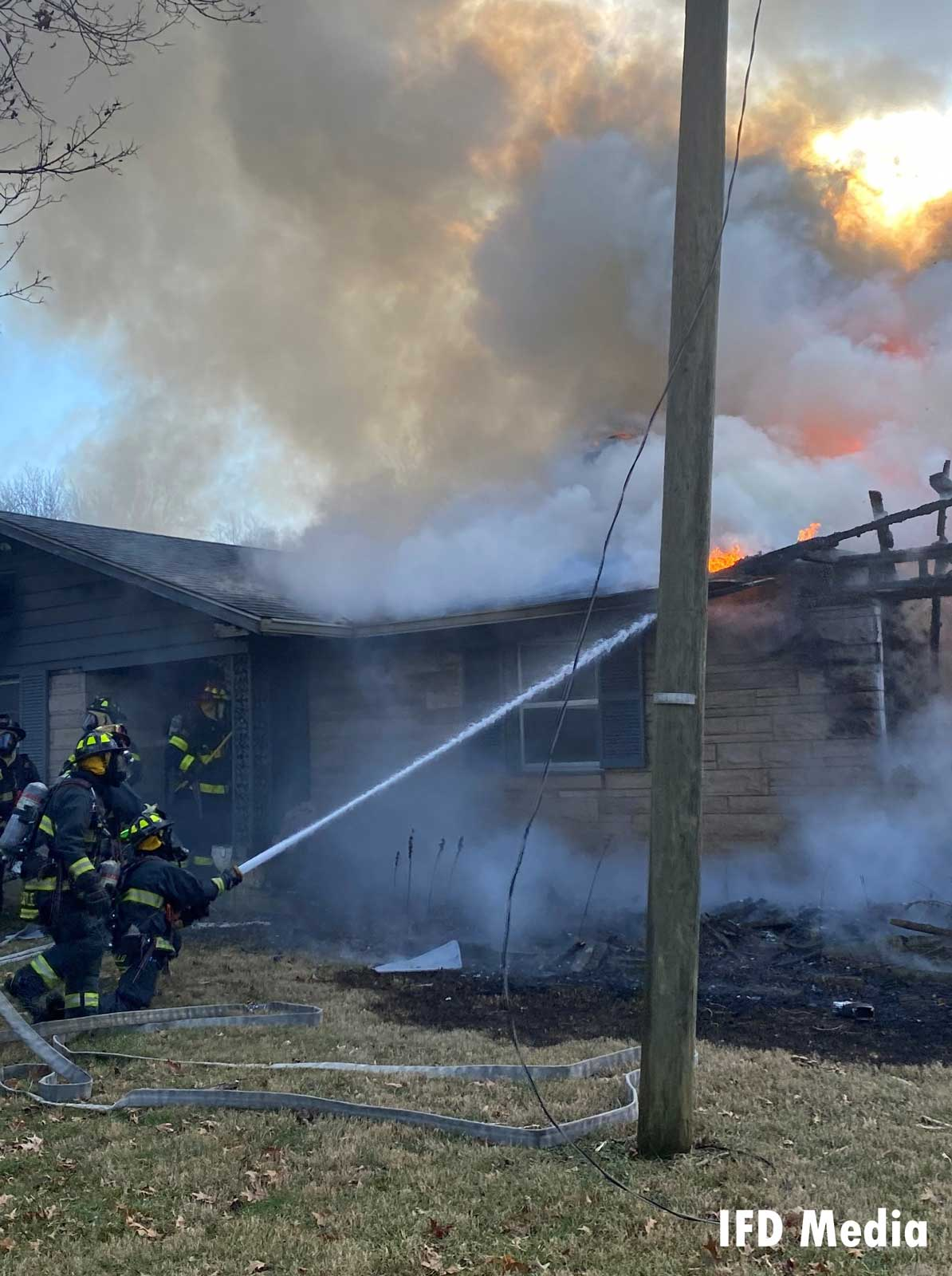 FIrefighters apply a hose stream to the fire from the outside