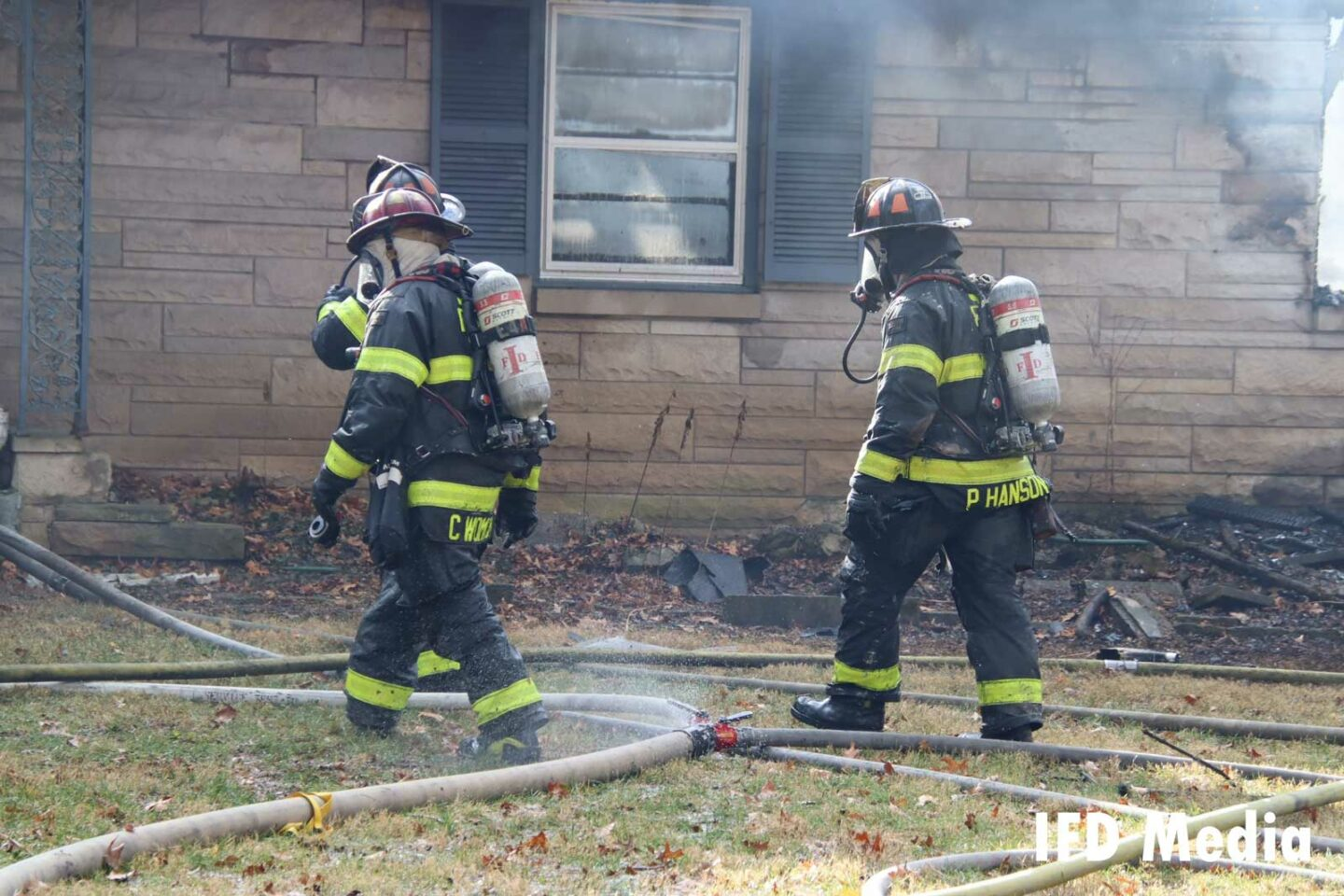Firefighters with hoselines on scene