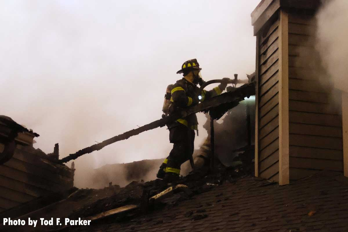 Firefighter with a hoseline on the roof