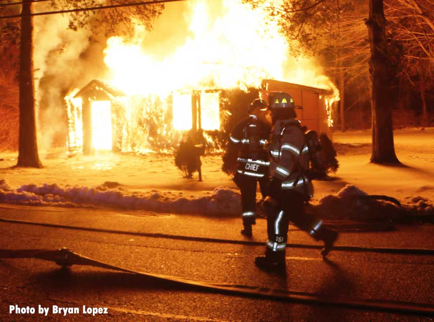 Firefighters race toward a fully engulfed home