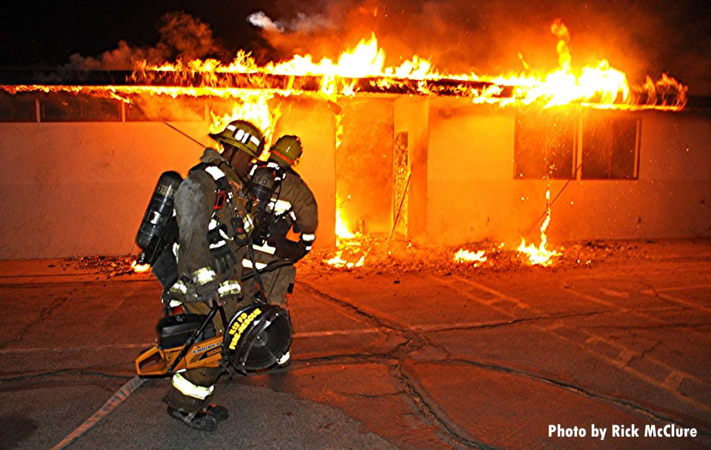 One firefighter with a circular saw and another with a hoseline as fire runs the roof