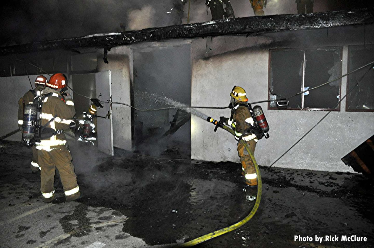 A firefighter with a hose sprays water into the building