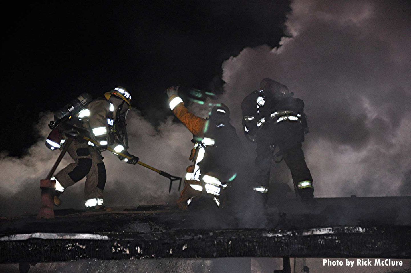 Firefighters open up a roof, partly obscured by smoke