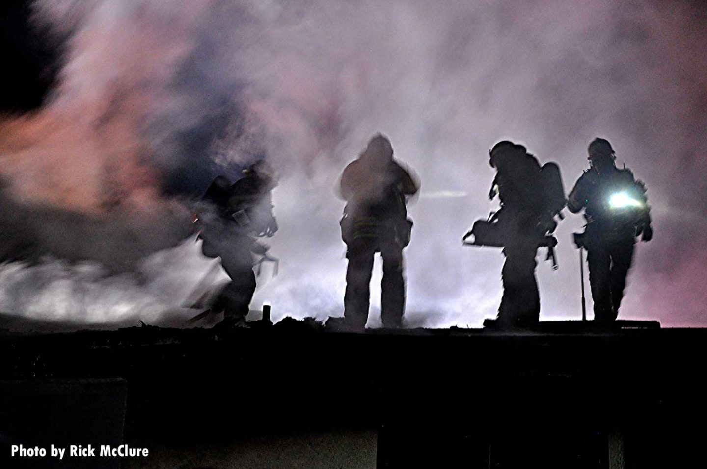 Firefighters working the roof silhouetted against smoke