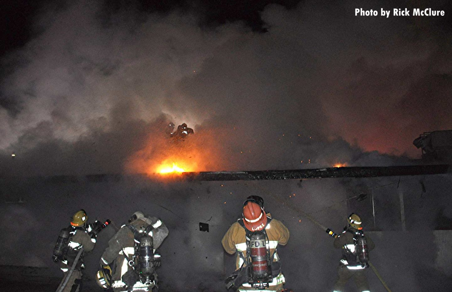 Smoke and flames from roofline with firefighters on the ground