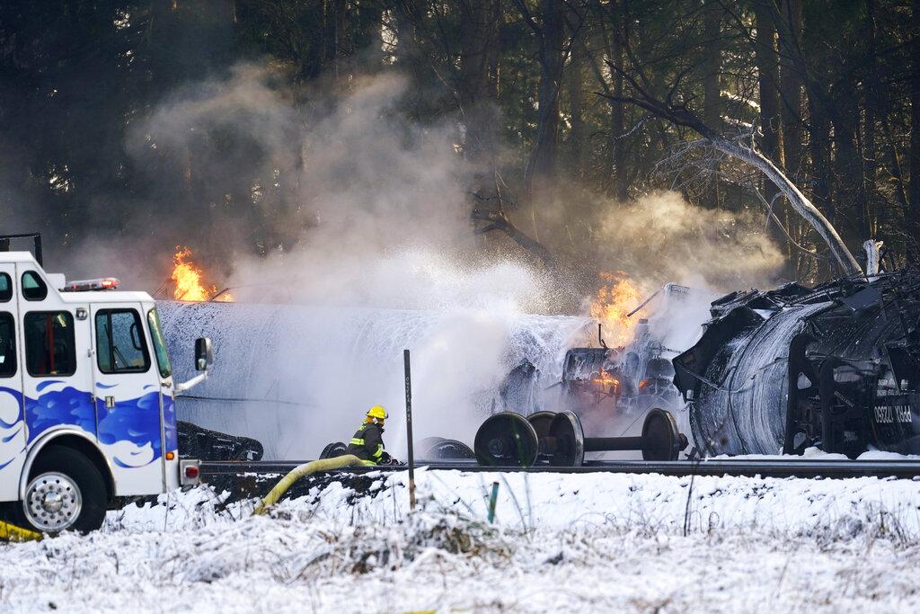 A firefighter sprays foam on burning, derailed train cars Tuesday, Dec. 22, 2020, in Custer, Wash.