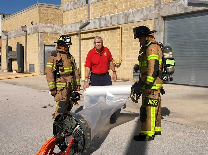 Bill Gustin and firefighters with a plastic duct and fan