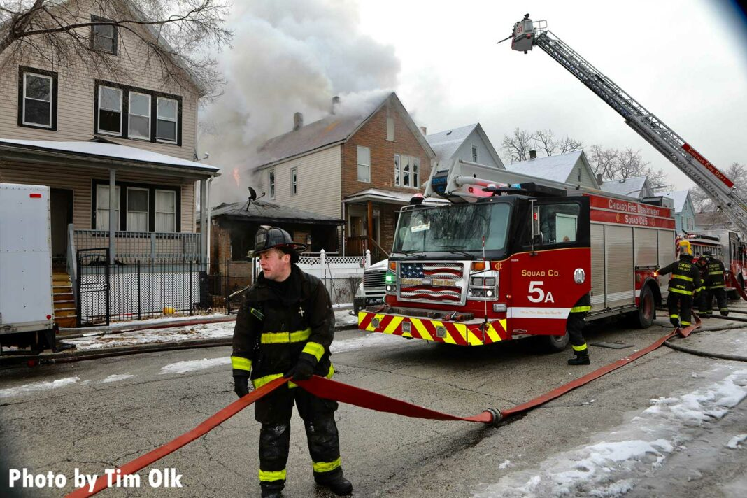 Chicago firefighter holding an LDH supply line at a house fire with Squad 5