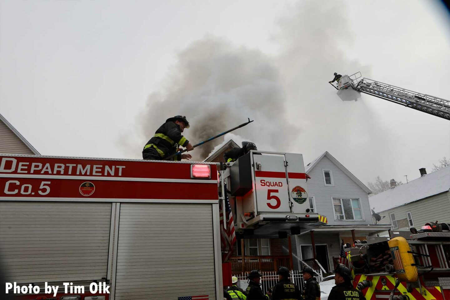 Chicago firefighter with a hook atop Squad 5 with Chicago firefighter in a tower ladder bucket in the background