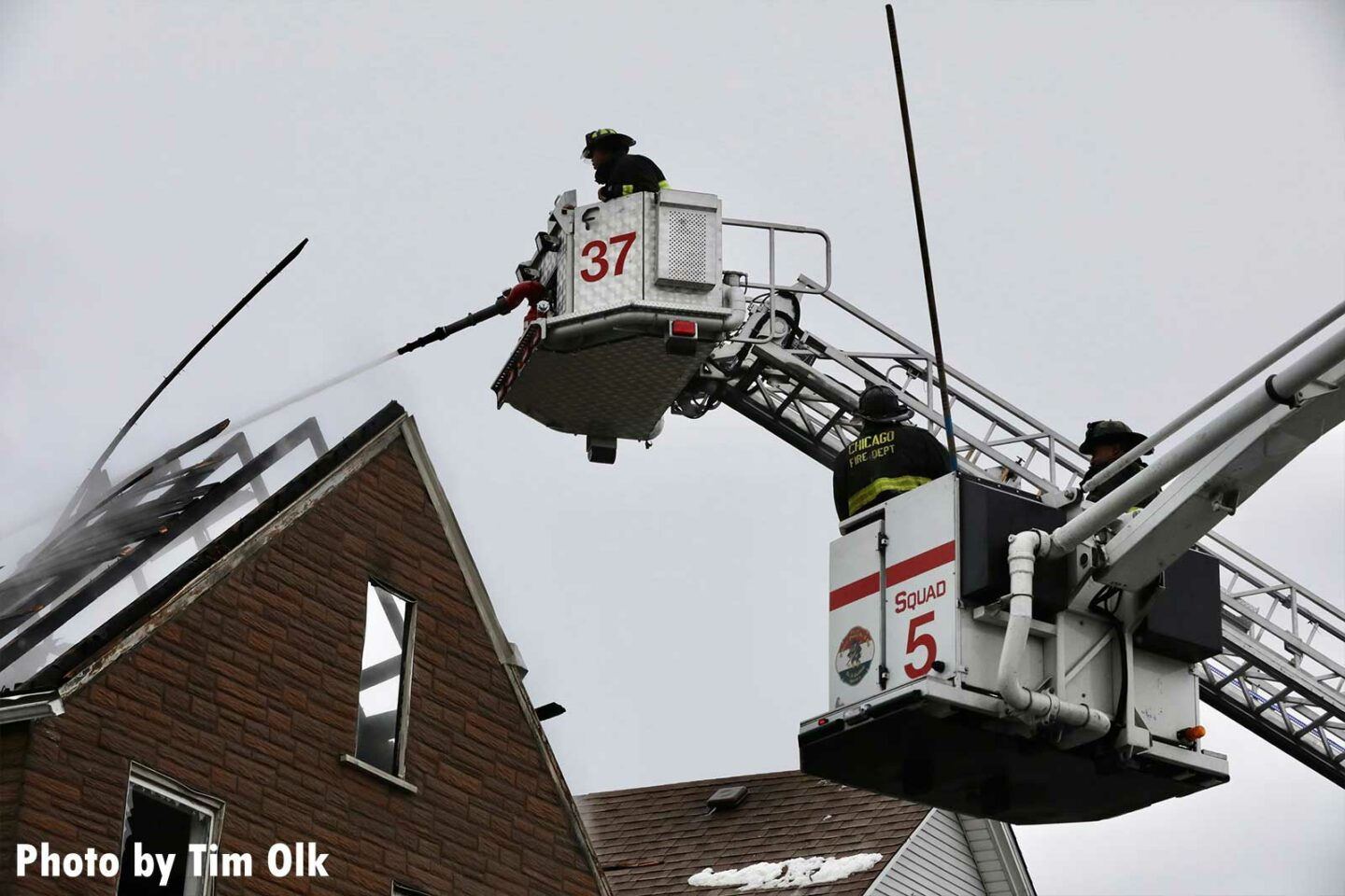Chicago firefighters operate from two buckets at a residential fire