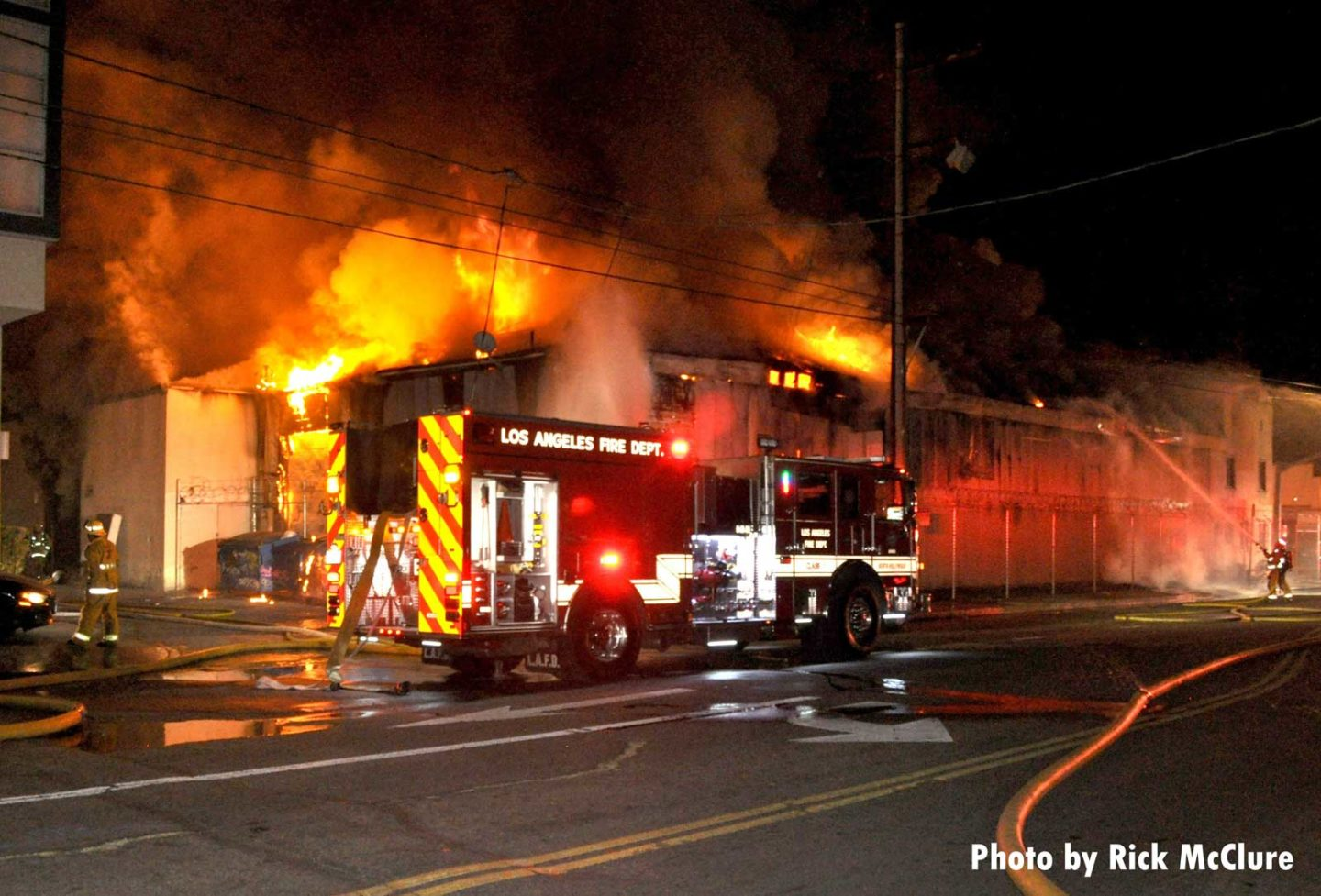 Major flames from a fire in a building with City of Los Angeles fire truck in front of structure