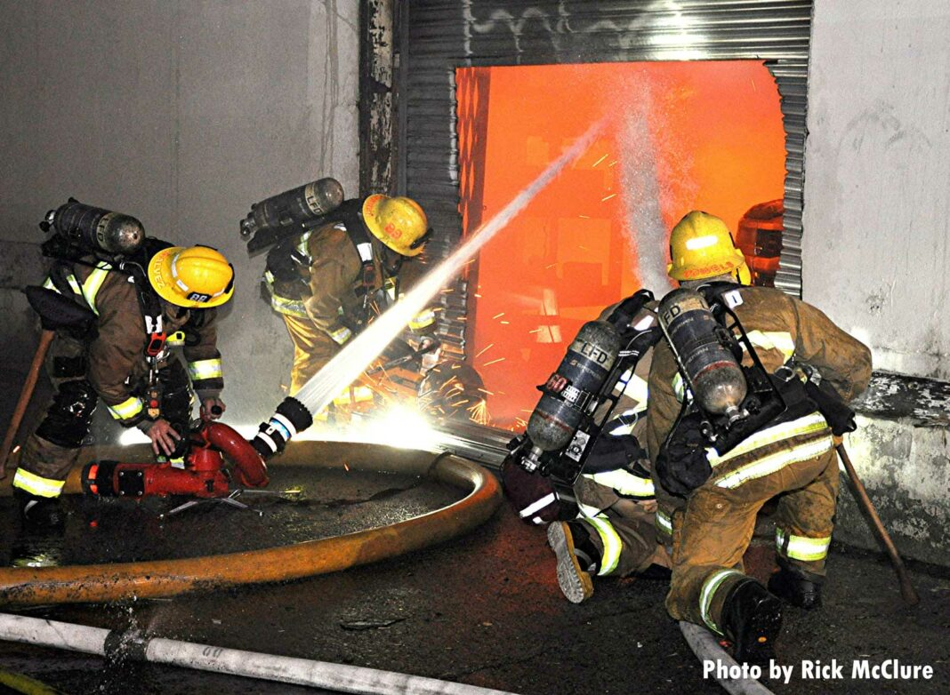 Two teams of LAFD firefighters with hoselines put water through a hole in a rolldown door