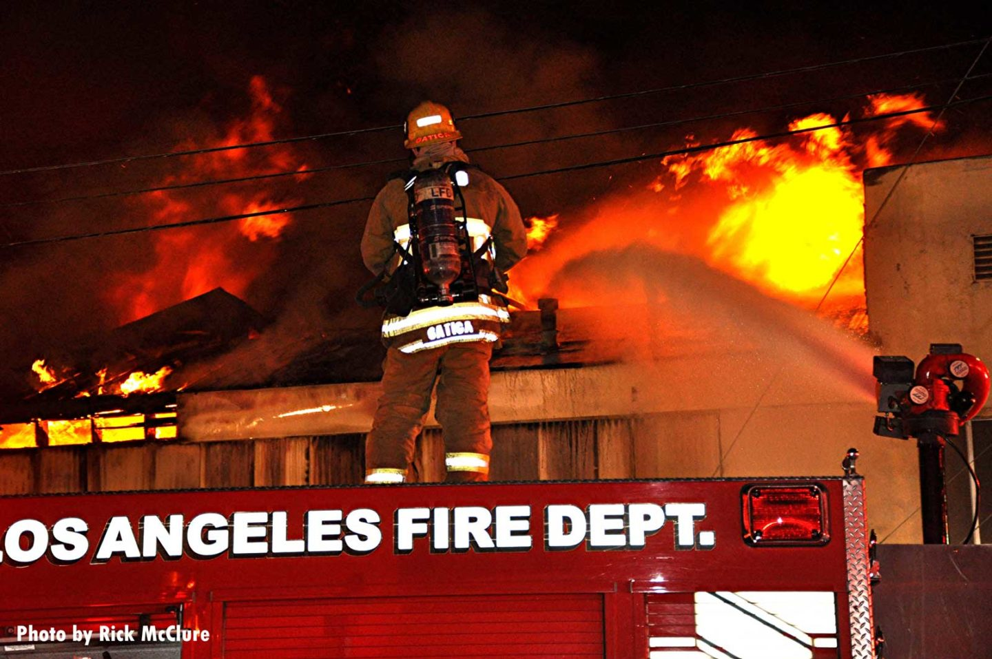 Flames shoot from the top of the building as firefighter observes from atop a Los Angeles City fire truck