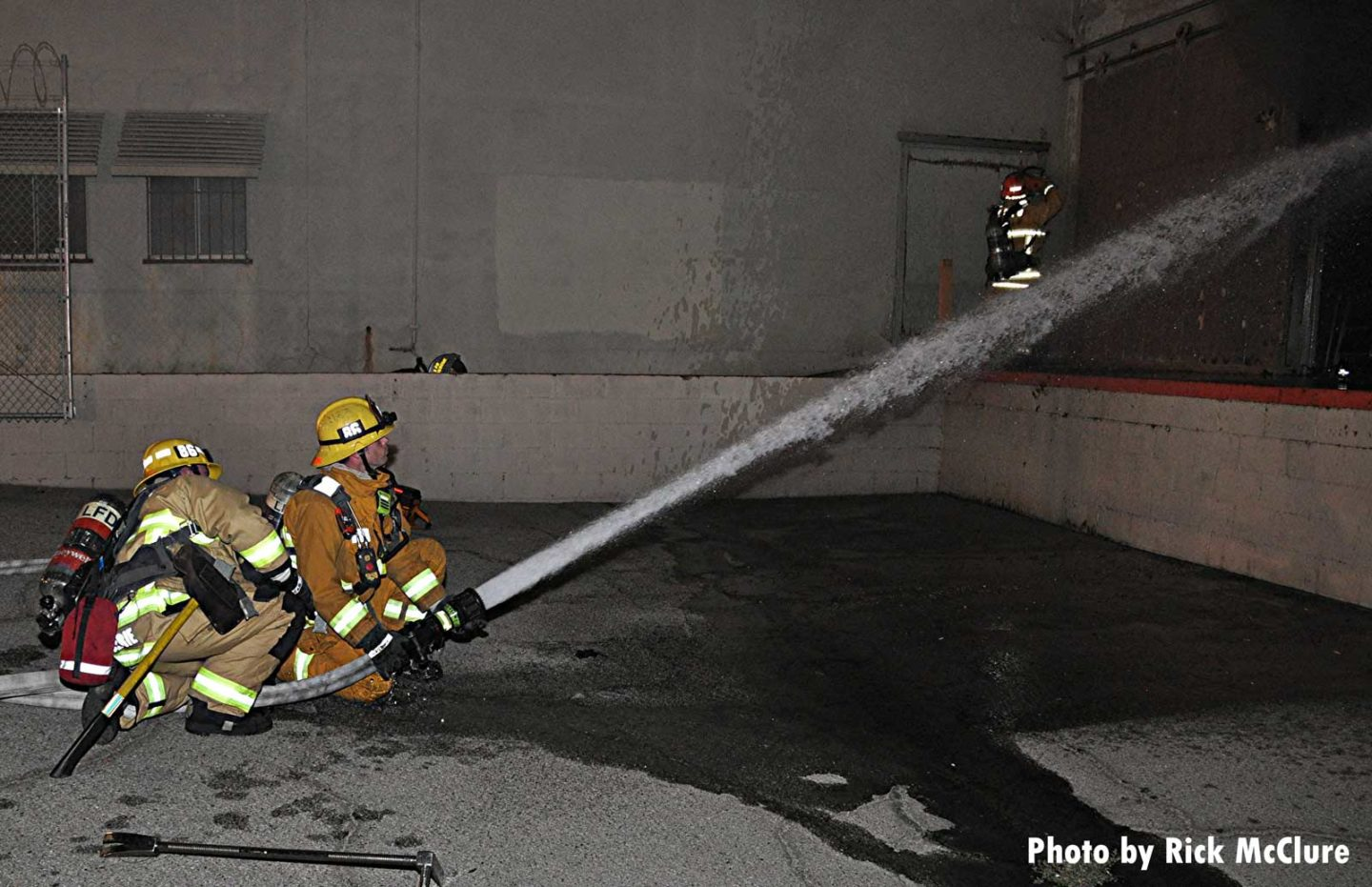 Two firefighters on a hoseline put water on the fire