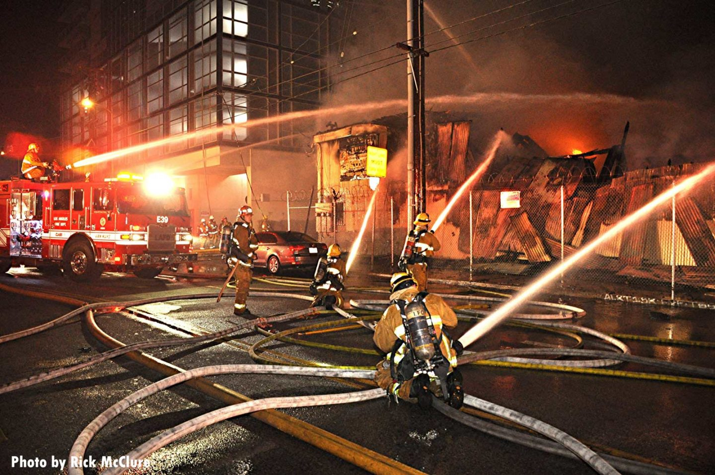 Firefighters with multiple hoses place water on the fire in Los Angeles