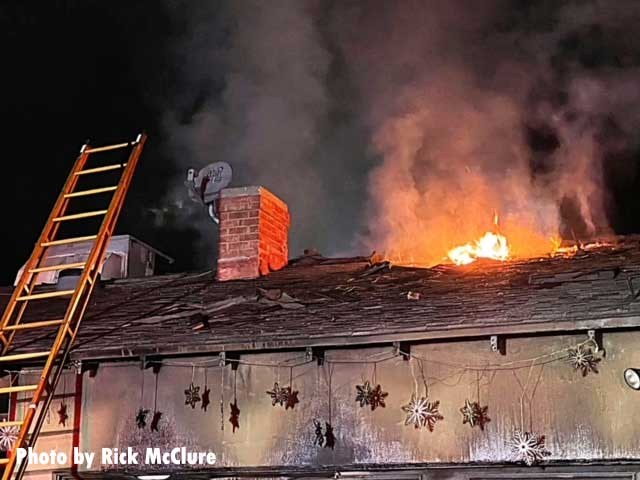 Flames emerge from the roof of the burning home