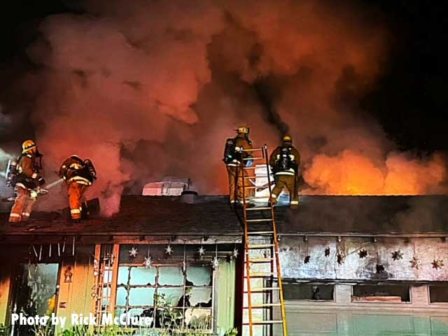 Four firefighters on the roof with a ladder and smoke showing